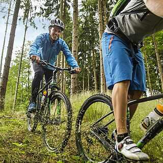 Sechs Personen fahren mit Helmen und Bikes durch einen Wald. Vorne weg fahren zwei Männer. Auf der rechten Bildseite fahren die Männer aus dem Bild.