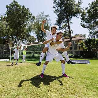 Menschen die sich beim Fußball über ein Tor freuen