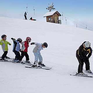 Vier Kinder und ein Trainer die aktiv im Winter Ski fahren