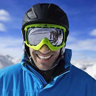 Mann mit Skibrille und Helm mit weißen Bergen im Hintergrund