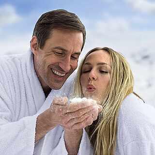 Frau und Mann targen einen Bademantel im Schnee und pusten den Schnee von der Hand des Mannes weg