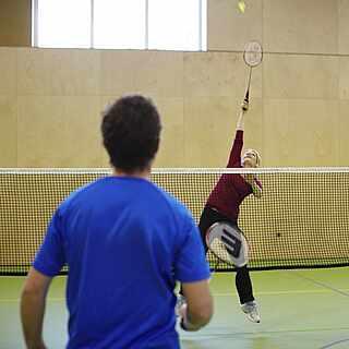 Zwei Gäste spielen Badminton in einer Halle