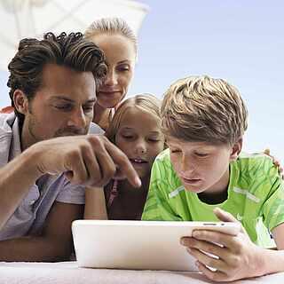 Vatrer, Mutter, Sohn und Tochter schauen zusammen interessiert auf ein Tablet