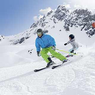 Eine Frau und ein Mann fahren auf Skiern die Piste hinunter