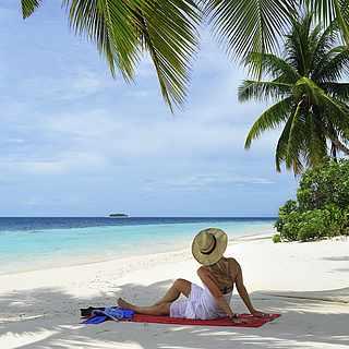 Frau sitzt am Strand, weißes Kleid, blaues Meer, Palmen, weißer Strand