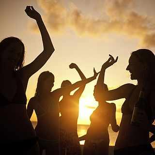 Ein Gruppe von Menschen tanzt beim Sonnenuntergang am Strand, nur die Silhouetten sind zu erkennen.