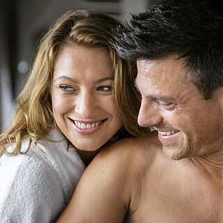 Frau in Bademantel umarmt ihren Mann
