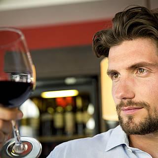 Gast schaut sich ein Glas Wein an und schaut wie der Wein abperlt