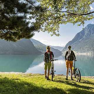 Zwei Personen stehen an einem See. Links und rechts von ihnen stehen Bäume. Der See ist von Gebirgen bzw. Fjorden umgeben.