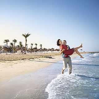 Mann trägt seine Frau am Strand auf Händen