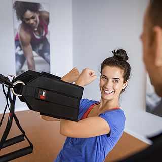 Frau beim GroupFitness mit Trainer