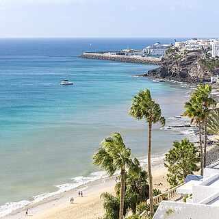 Blick auf Küste und türkises Meer mit Palmen und weißen Gebäuden