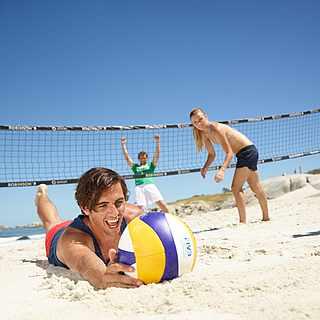 Drei Personen spielen Volleyball, wobei einer von ihnen dem Ball hinterspringt