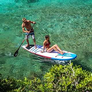 Ein Paar, wo der Mann paddelt und die Frau das Wetter genießt.