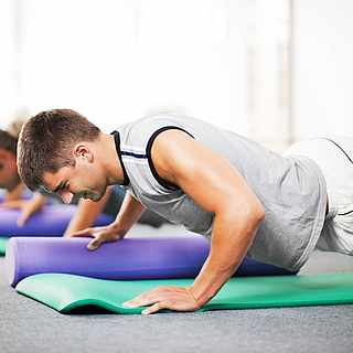 Gruppe bei Kraft-Übungen auf der Fitnessmatte