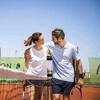 Paar umarmt sich beim Tennis