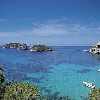 Blick auf klares, türkises Meer mit schroffen Felsen und Booten unter blauem Himmel