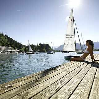 Langer Holzsteg,Frau im Bikini,großes Segelboot im Hintergrund auf den Ossiacher See
