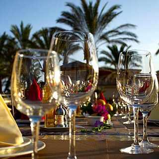 Mehrere Gläser stehen auf einem Tisch. Im Hintergrund sieht man Palmen.