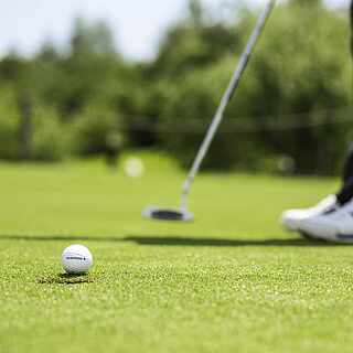 Golfspieler von den Knien abwärts kurz vorm Abschlag