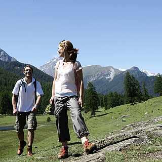 Zwei Personen wandern auf einer schrägen Ebene. Im Hintergrund sieht man eine Gebirgslandschaft.