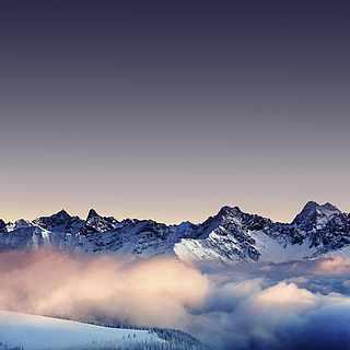 Hohe verschneite Berge, die im Nebel liegen