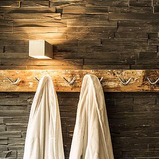 Man sieht eien Sauna und vor der Sauna hängen 2 Bademäntel