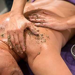 Frauenbeine werden von einer Masseurin massiert