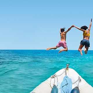 Pärchen springt vom Boot ins klare Wasser mit Rabatt-Hinweisen
