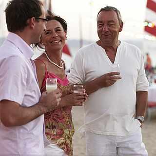 Zwei Paare trinken und lachen am Strand