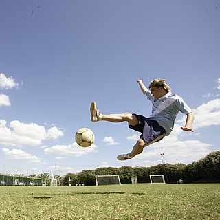 Ein Mann springt hoch und schießt den Ball bei gutem Wetter