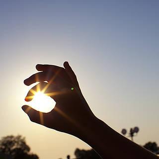Hand formt mit den Fingern einen Kreis, welcher die Konturen der Sonne umramt