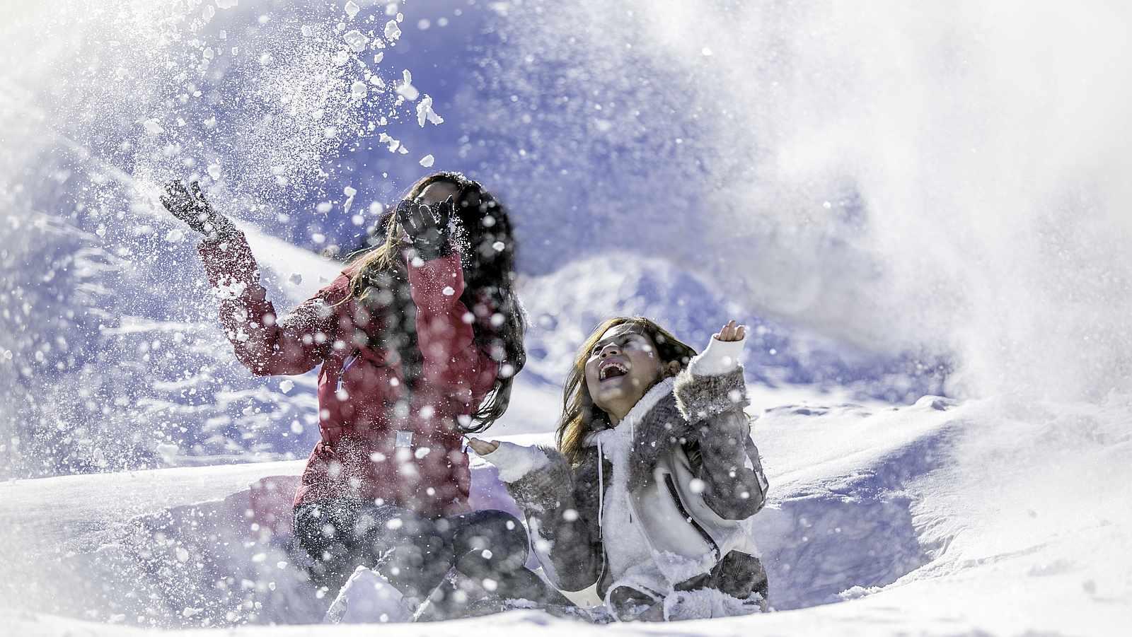 Zwei Frauen werfen Schnee in die Luft