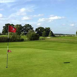 Gepflegter Golfplatz unter blauem Himmel mit roter Fahne im Vordergrund