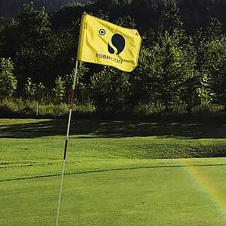 Golfplatz mit Bergausblick und gelber Fahne
