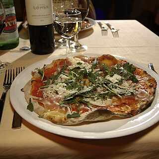 Ein Teller mit einer Pizza auf einem eingedeckten Tisch