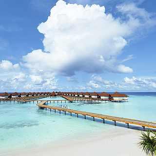 Steg über einen paradiesischen Strand ins Wasser hin zu kleinen Hütten auf dem Meer
