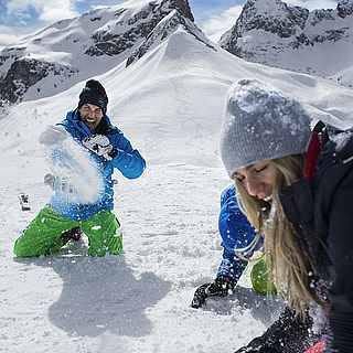 Zwei Menschen liegen im Schnee und strecken ihre Skier in die Luft