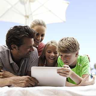 Familie sitzt vor dem Tablet und informiert sich über die ROBINSON Apps