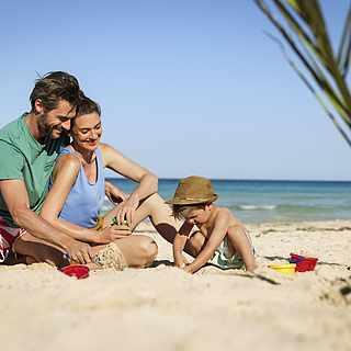 Eltern spielen mit ihrem Kind am Strand
