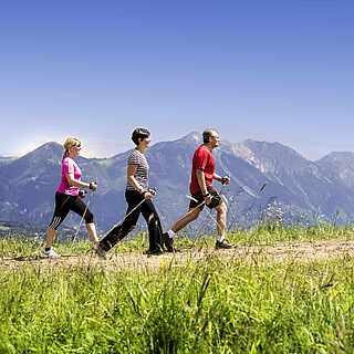 Drei Personen laufen mit Walkingstöcken auf einem Weg entlang. Sie sind umgeben von einer Gebirgslandschaft, Wiesen und Bäumen.