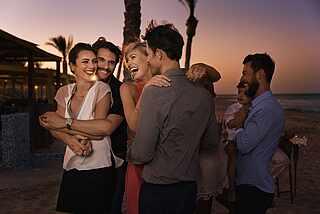 Menschen tanzen und lachen am Strand