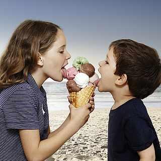 Zwei Kinder schlecken ein großes Eis am Strand