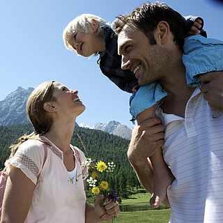 Eine kleine Familie hat Spaß in einer Gebirgslandschaft. Die Frau hat Blumen in der Hand.