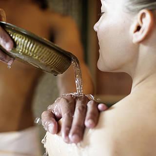 Ein Mann gießt einer Frau etwas über die Schulter