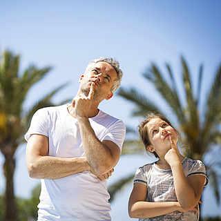 Vater und Tochter stehen vor Palmen und halten nachdenklich eine Hand ans Kind