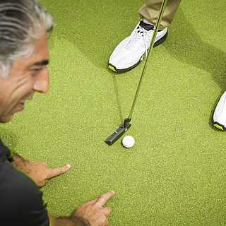 Golflehrer erklärt am Boden einen Golfschlag