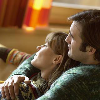 Paar sitzt zusammen auf einer Couch und umarmt sich