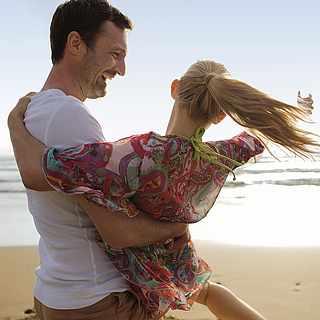 Am Strand sind ein Mann und eine Frau, wobei der Mann die Frau auf den Armen hält und sie sich zusammen im Kreis drehen
