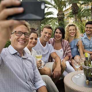 Reisegruppe macht ein Selfie unter Palmen